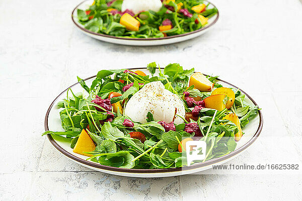 Two plates of vegetarian salad with fruits  vegetables and burrata cheese
