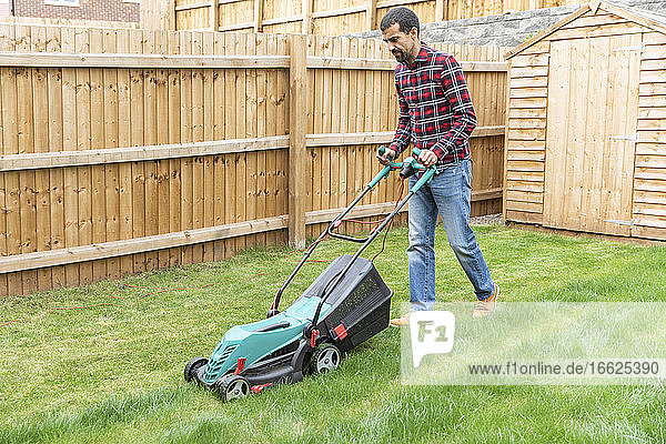 Mid adult man cutting grass with lawn mower at backyard