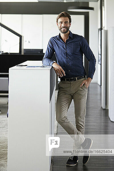 Businessman smiling while standing at office
