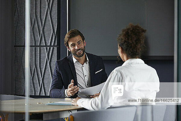 Smiling businessman discussing with colleague in meeting at office