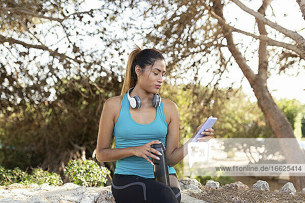 Beautiful young woman using smart phone while holding water bottle against trees