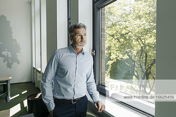 Businessman looking through window while standing at office