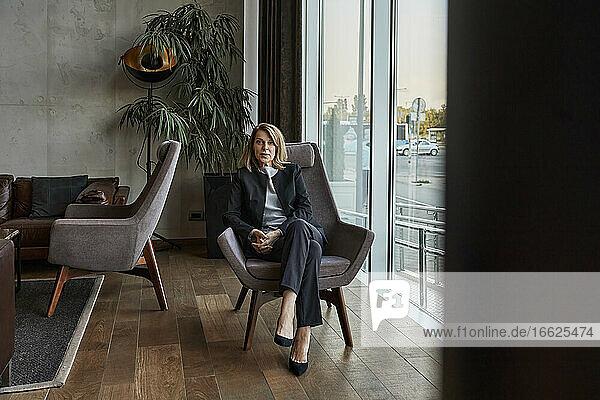 Ernste ältere Frau sitzt auf einem Stuhl in der Hotellobby Ernste ältere Frau sitzt auf einem Stuhl in der Hotellobby