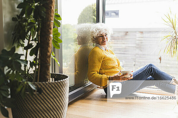 Mature woman sitting with coffee cup at home
