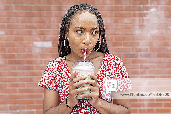 Young woman drinking smoothie while standing against brick wall