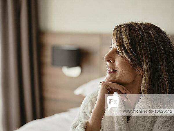 Nachdenklich lächelnde blonde Frau  die wegschaut  während sie in einem Hotelzimmer sitzt Nachdenklich lächelnde blonde Frau, die wegschaut, während sie in einem Hotelzimmer sitzt