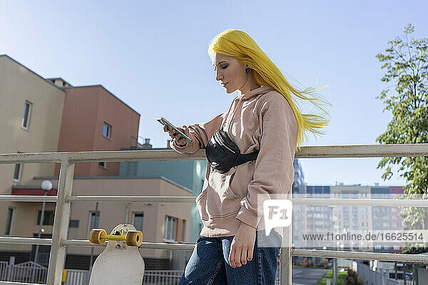 Young woman text messaging on smart phone while standing on bridge