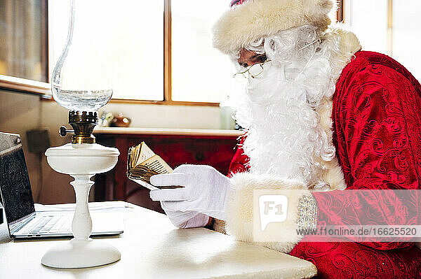 Man wearing Santa Claus costume with laptop on table reading bible while sitting at home