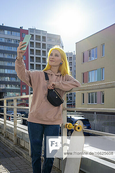Young woman taking selfie on smart phone while standing during sunny day