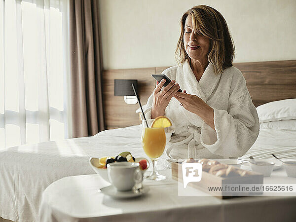 Smiling blond senior woman using smart phone while sitting with breakfast in hotel room