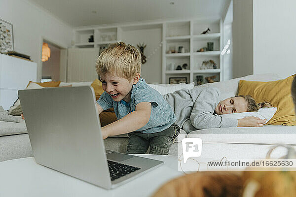 Boy using laptop by mother sleeping on sofa at home