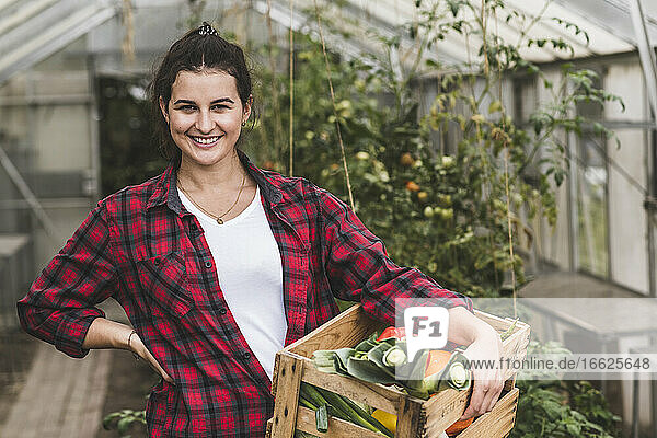 Smiling woman carrying vegetable crate while standing against greenhouse