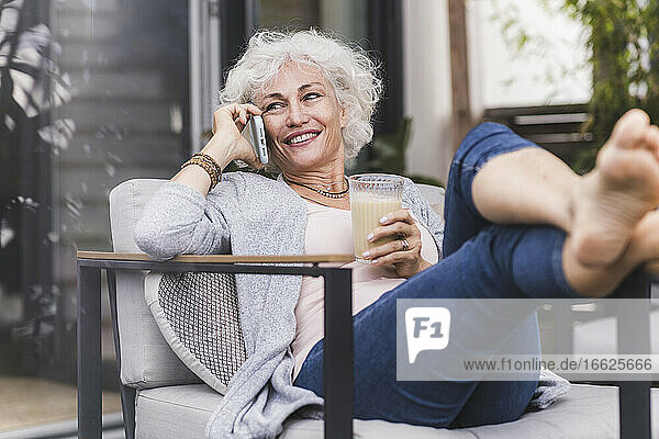 Mature woman talking on smart phone while holding juice sitting at home