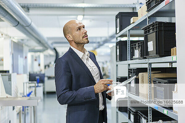 Mature male professional with digital tablet looking at containers on rack in industry
