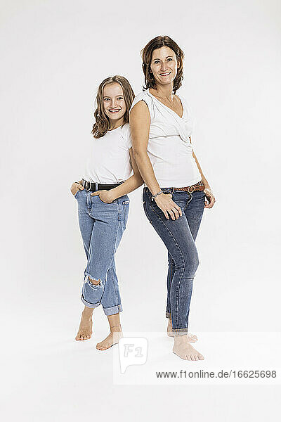 Smiling mother and daughter with hands in pockets posing while standing against white background