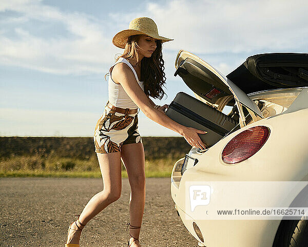 Schöne junge Frau  die einen Koffer aus dem Kofferraum nimmt Schöne junge Frau, die einen Koffer aus dem Kofferraum nimmt
