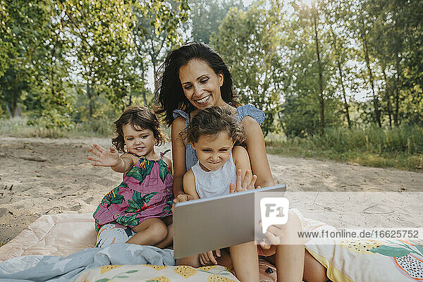 Mother and daughters doing video call on digital tablet