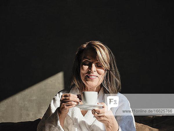 Lächelnde blonde Frau genießt frischen Kaffee in einem Hotelzimmer Lächelnde blonde Frau genießt frischen Kaffee in einem Hotelzimmer