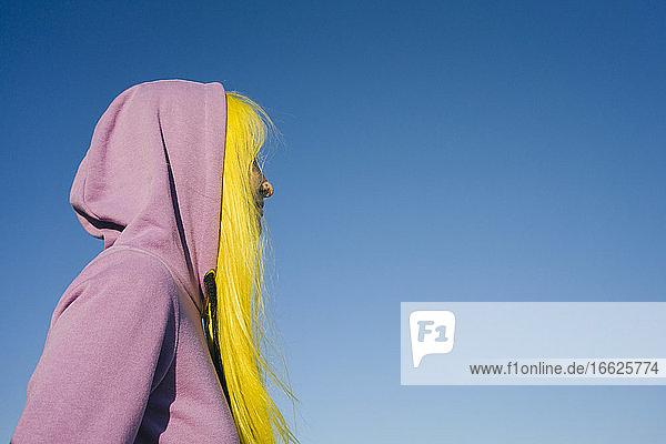 Frau mit Kapuzenshirt schaut weg  während sie an einem sonnigen Tag vor einem klaren Himmel steht Frau mit Kapuzenshirt schaut weg, während sie an einem sonnigen Tag vor einem klaren Himmel steht