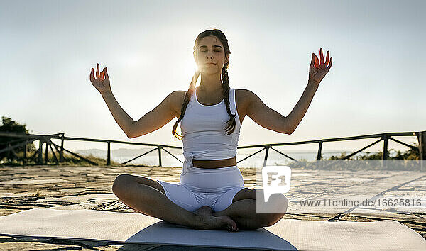 Young woman with arms raised meditating on mat against clear sky at sunset