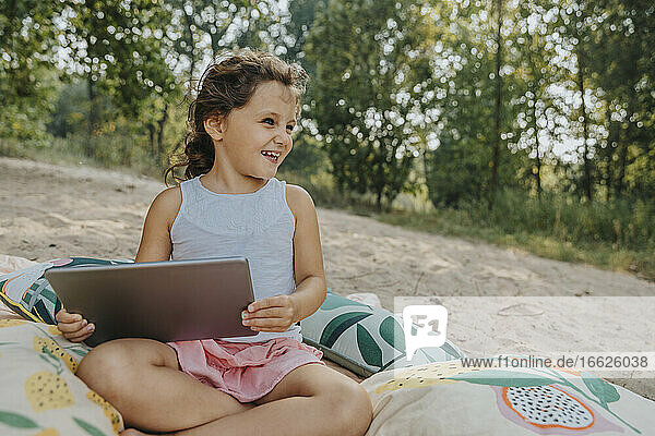 Smiling cute girl looking away while holding digital tablet