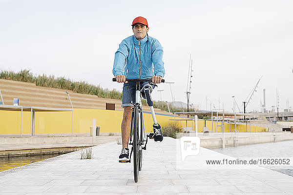 Young man with artificial limb and foot riding bicycle on footpath against clear sky