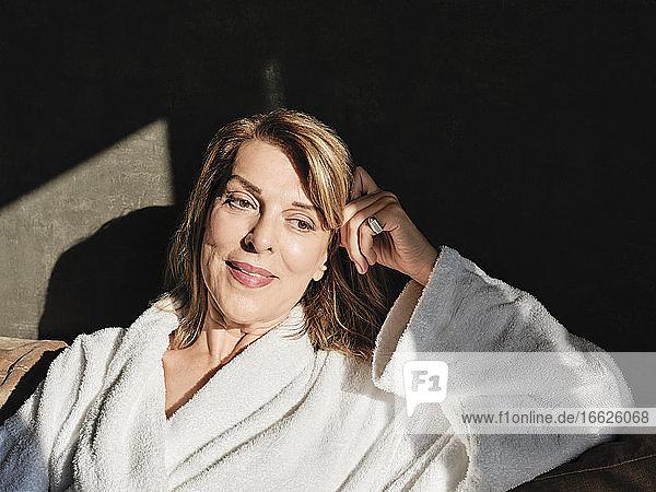 Nachdenkliche schöne blonde Frau schaut weg  während sie sich auf dem Sofa im Hotel entspannt Nachdenkliche schöne blonde Frau schaut weg, während sie sich auf dem Sofa im Hotel entspannt