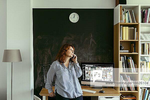 Frau  die am Schreibtisch stehend zu Hause mit einem Mobiltelefon spricht Frau, die am Schreibtisch stehend zu Hause mit einem Mobiltelefon spricht