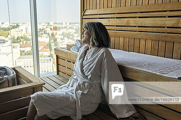 Senior woman wearing bathrobe looking away while sitting on wooden sofa