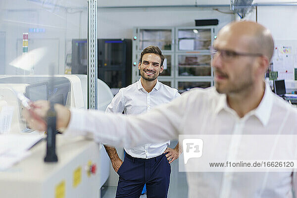 Smiling engineer looking at technician in illuminated laboratory