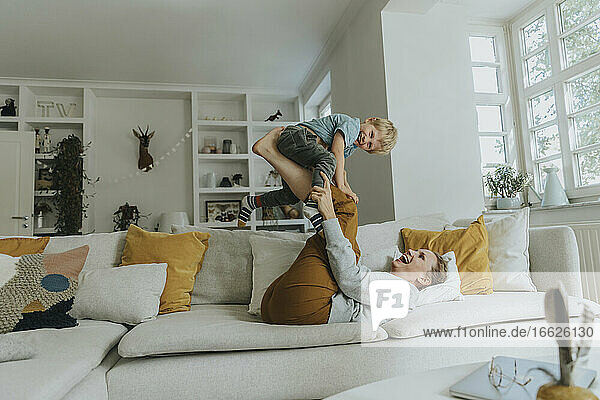 Mother picking son on leg while playing on sofa at home
