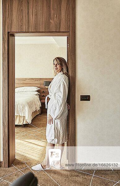 Schöne ältere Frau im Ruhestand  die an der Tür eines Hotelzimmers steht Schöne ältere Frau im Ruhestand, die an der Tür eines Hotelzimmers steht
