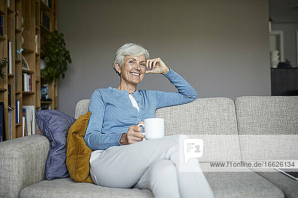 Smiling senior woman sitting on sofa holding coffee cup at home