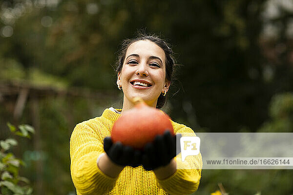 Woman holding pumpkin in hand while standing at urban garden