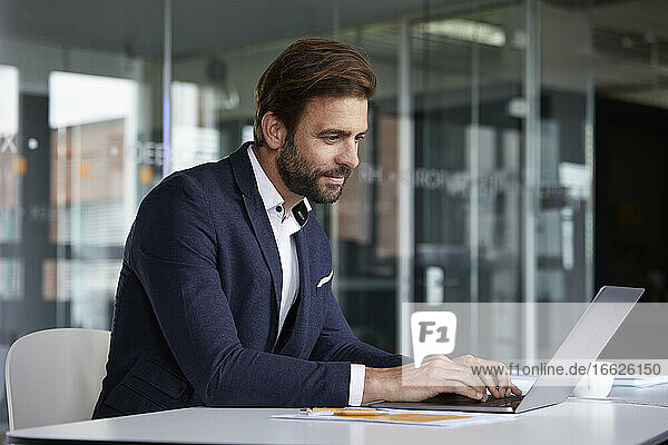 Businessman working on laptop while sitting at office