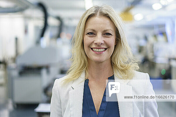 Smiling mature blond female professional standing at illuminated industry