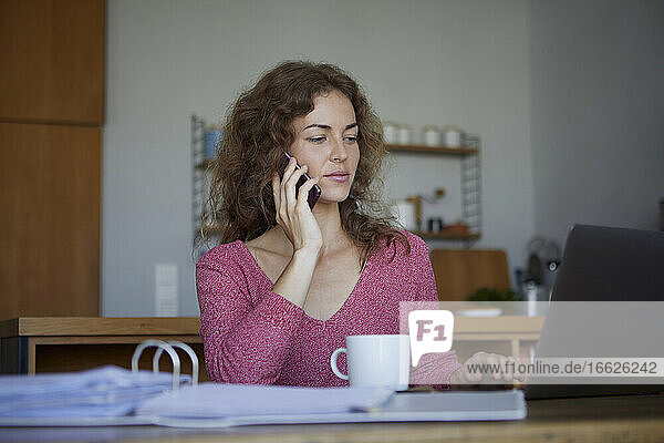 Woman working while sitting by table at home