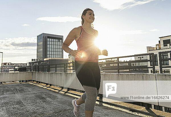 Female athlete running on terrace against sky in city