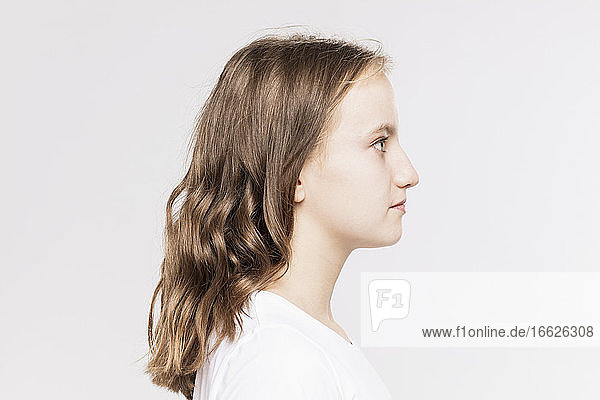 Close-up of thoughtful girl looking away against white background
