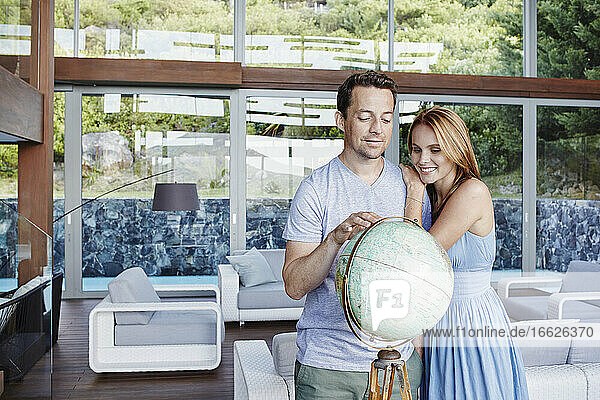 Couple looking at globe while standing in modern house
