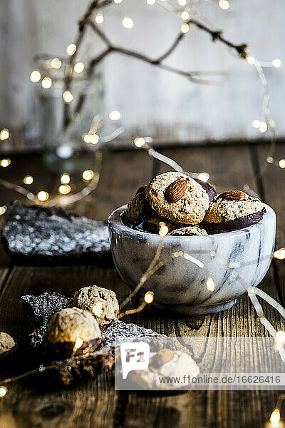 Christmas lights and bowl ofgingerbread cookies with almonds