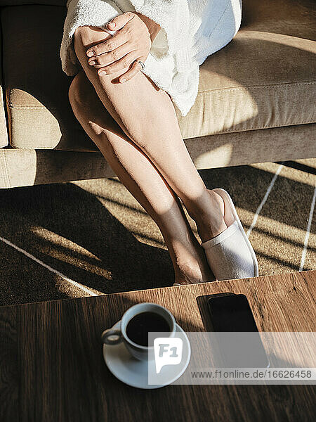 Coffee and smart phone on table by senior woman sitting in hotel room