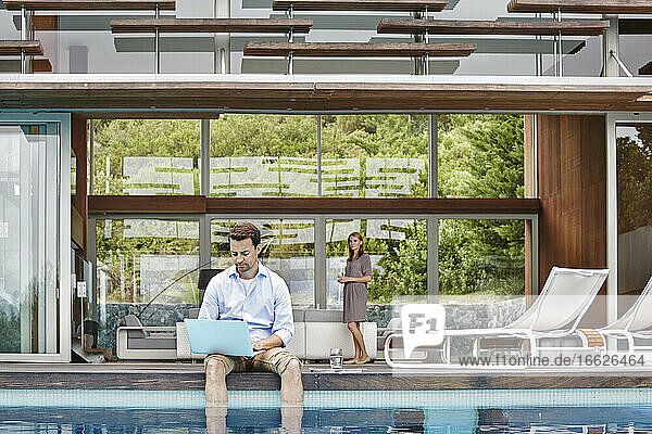Mature man working on laptop while sitting against modern house