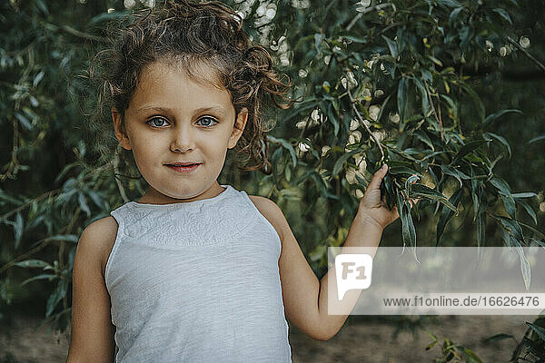 Cute little girl standing under willow tree