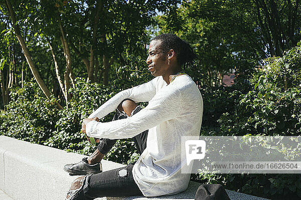 Man sitting on retaining wall at park