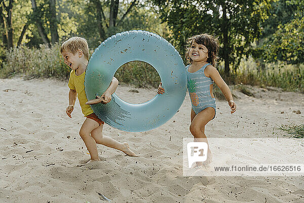 Children running with inflatable ring at beach