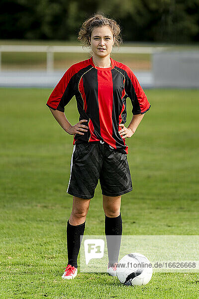 Female player with soccer ball standing on field