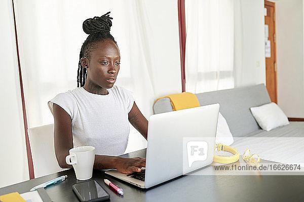 Junge Geschäftsfrau arbeitet an einem Laptop auf dem Schreibtisch  während sie im Büro zu Hause sitzt Junge Geschäftsfrau arbeitet an einem Laptop auf dem Schreibtisch, während sie im Büro zu Hause sitzt