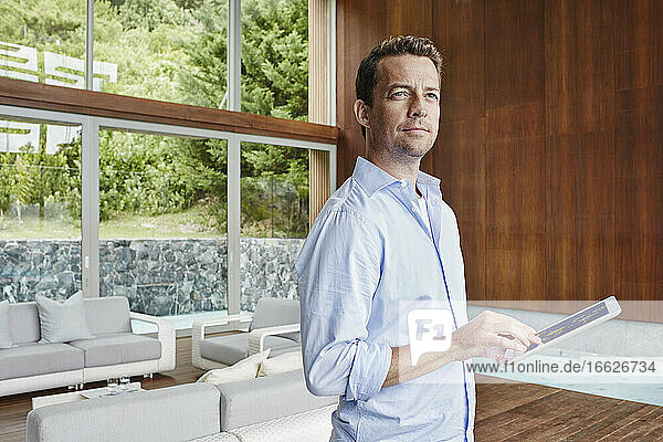 Man looking away while using digital tablet standing at home
