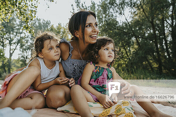 Mother and daughters looking away while sitting at beach